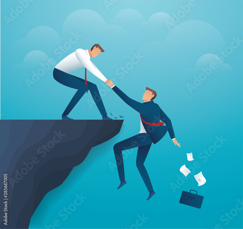 Fotografiet man holding partner hands hanging cliff help concept together