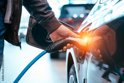 Human hand is holding Electric Car Charging connect to Electric car - 283667263