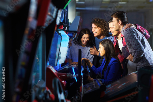 A group of friends playing arcade machine. Fotobehang