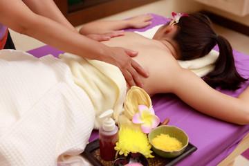 Obraz na płótnie Canvas Asian woman enjoying a salt scrub massage at spa.