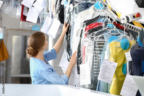 Fotografía  Worker of modern dry-cleaner's near rack with clothes