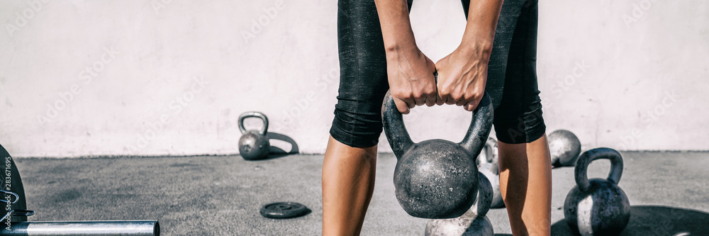 Fototapeta Kettlebell weightlifting woman lifting free weight panoramic banner gym. Hands holding heavy kettle bell for strength training exercise lifestyle.