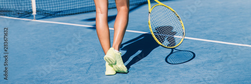 Fotografía  Tennis player woman shoes and racket on blue hard court background panoramic banner of athlete ready to play game