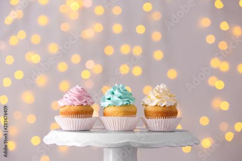 Photo  Tasty Birthday cupcakes on stand against defocused lights