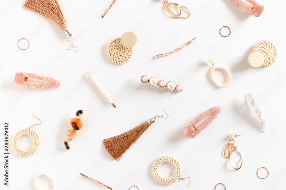 Fototapeta Pattern made of earrings, rings, hairpins on white background