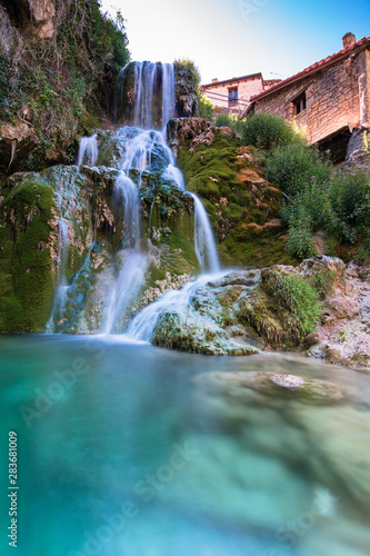 Fotobehang Bos rivier Famous waterfalls with silk effect with a crystalline water running between the houses and flowing to the Ebro river in Orbaneja del Castillo (Burgos, Spain)