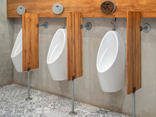 Three Modern White Automatic Urinal For Men And Wood Partitions On Cement Wall In Toilet.