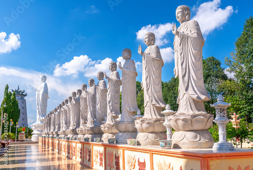 Obraz Beauty architecture leads to Lord Buddha statue shining in Dai Tong Lam Pagoda, which attracts tourists to visit spiritually on weekends in Vung Tau, Vietnam - fototapety do salonu