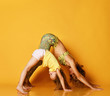 Young mother and daughter doing yoga exercises together in a fitness studio on a yellow background