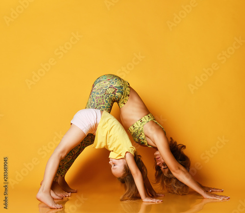 Poster Ecole de Yoga Young mother and daughter doing yoga exercises together in a fitness studio on a yellow background
