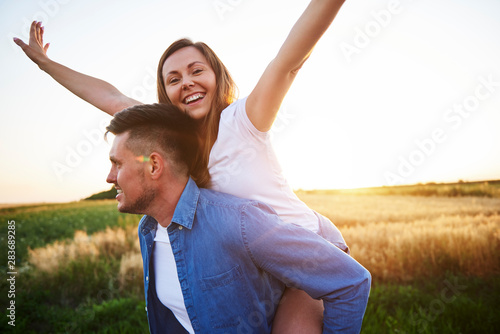 Fotomural  Happy man carrying girlfriend on his shoulders