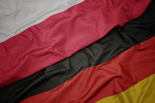 Waving Colorful Flag Of Germany And National Flag Of Poland.