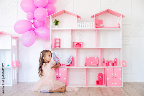 Fotografia, Obraz Cute happy girl in a beautiful dress at home plays with a dollhouse and toys
