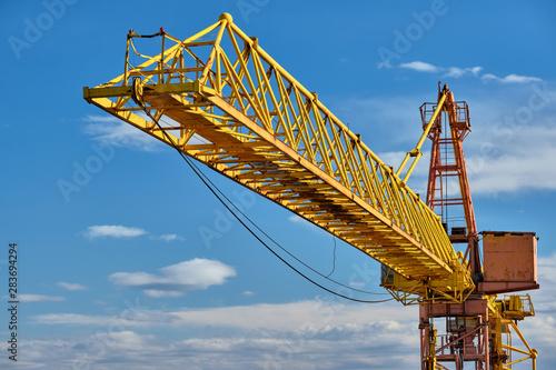 Canvas Print Yellow construction jib crane tower against blue sky
