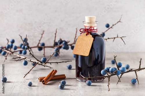 Valokuva Bottle of homemade sloe liqueur with cinnamon as a small gift