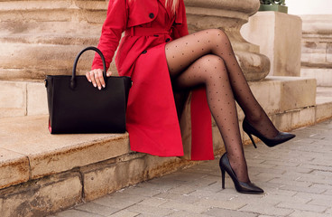 Fashion model in red coat with big black bag in heel shoes