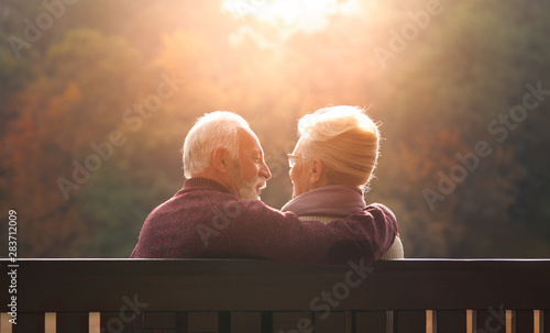 Obraz na plátně Senior couple sitting on bench in autumn park