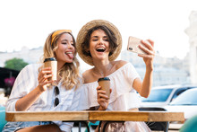 Cutie Cheery Young Optimistic Girls Friends Sitting Outdoors In Cafe Drinking Coffee Take Selfie By Mobile Phone.