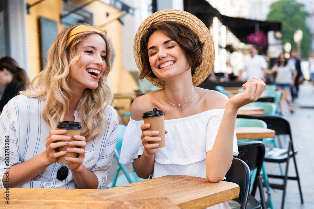 Obraz Happy young positive optimistic girls friends sitting outdoors in cafe drinking coffee talking with each other. fototapeta, plakat