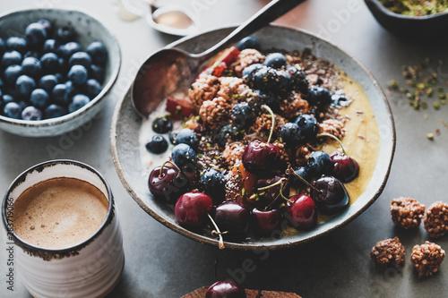 Fototapeta Healthy vegan breakfast set. Quinoa oat granola coconut yogurt bowl with fruit, seeds, nuts, berries and coffee over grey concrete background, selective focus. Vegetarian, dieting food concept obraz
