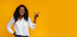 Leinwanddruck Bild - Cheerful black girl pointing at empty space