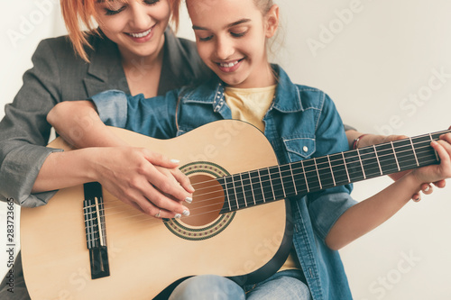 Photo sur Toile Les Textures Smiling woman teaching girl to play guitar