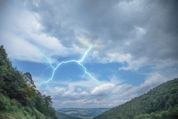 Dramatic scene of thunderstorm with lightning in dark stormy sky in mountains