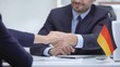 German boss signing employment contract with immigrant employee, shaking hand