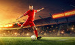canvas print picture - Soccer player in action with a ball on a stadium