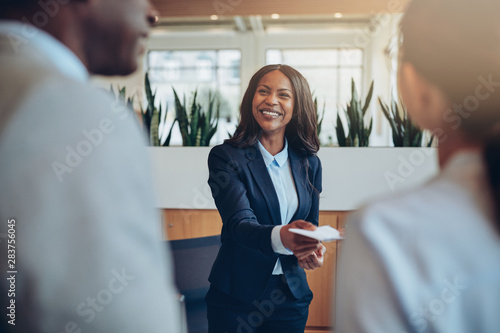 Smiling young African American hotel concierge helping guests ch