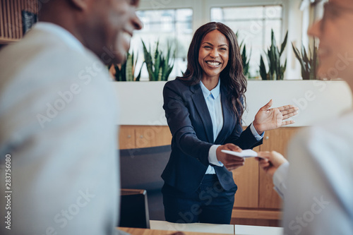 Fototapeta Laughing young African American hotel concierge helping guests c