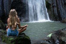 Aerial Drone View Back Of Woman Meditating At The Beautiful Waterfall In Green Tropical Rain Forest In Bali, Indonesia