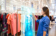 canvas print picture - futuristic technology concept.happy girl try to use smart hologram display with virtual augmented reality in the shop or retail to choose select ,buy clothes and change a color of products.