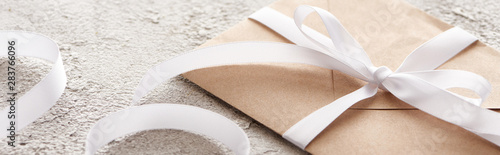 Fotografie, Obraz  panoramic shot of beige envelope with white ribbon on textured surface