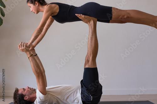 Profesora y aprendiz realizando yoga en interior Wallpaper Mural
