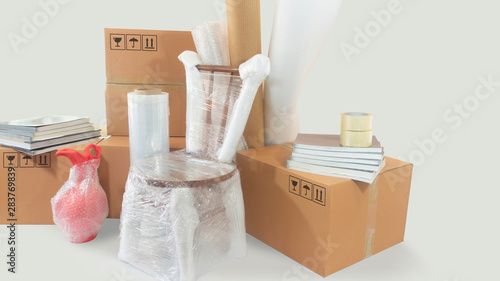 Fotografía  Moving scene with a chair and vase packed in plastic bubble with closed cardboar