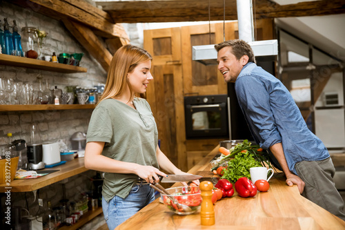 Fotografie, Obraz  Beautiful young couple smiling while cooking in kitchen at home