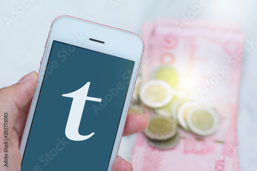 Photo  hand hold smartphone showing T alphabet on green screen and money in the backgro