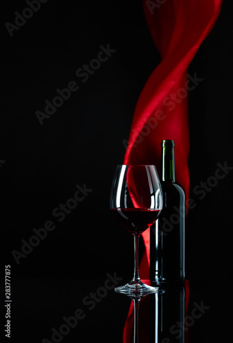 Fotografie, Obraz  Wineglass and bottle of red wine on a black reflective background