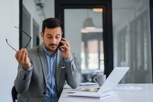 Stressed Out Businessman In Office Making Important Phone Call About Serious Problem Working Under Pressure And Tight Deadline