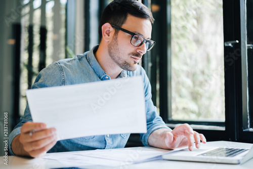 Serious pensive thoughtful focused young casual business accountant bookkeeper i Wallpaper Mural