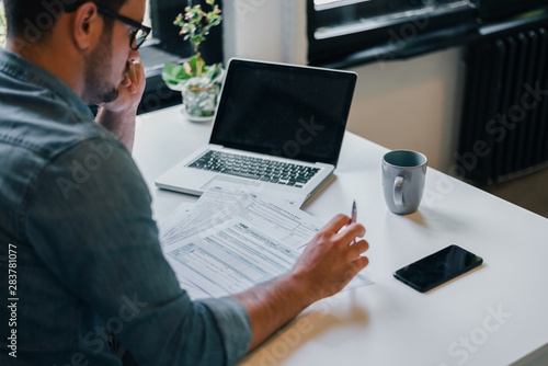 Obraz Serious pensive thoughtful focused young casual businessman or entrepreneur in office filling income tax return papers documents for IRS - fototapety do salonu