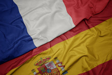 Waving Colorful Flag Of Spain And National Flag Of France.