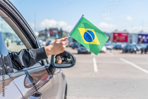 Fototapeta  Boy holding Flag of Brazil from the open car window on the parking of the shopping mall