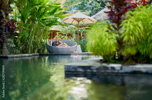Obraz Candid shot of young caucasian couple lounging in modern chair near luxurious pool of tropical hotel and spa in Bali - fototapety do salonu