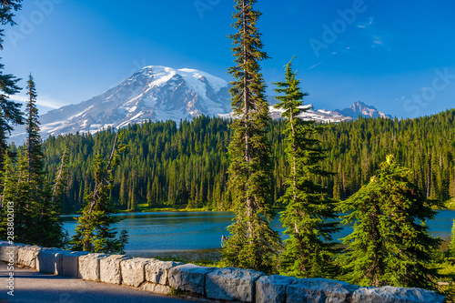 Overlooking a lake and a forest of pine trees with Mt. Rainier looming in the distance at Mt. Rainier National Park.