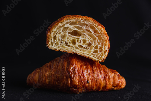 Fotografia A croissant cut in half on top of a full croissant on black background