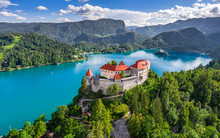 Bled, Slovenia - Aerial Panoramic View Of Beautiful Bled Castle (Blejski Grad) With Lake Bled (Blejsko Jezero), The Church Of The Assumption Of Maria And Julian Alps At Background On A Summer Day