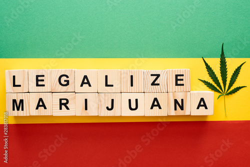 Obraz na plátně  top view of cannabis leaf and wooden blocks with legalize marijuana lettering on