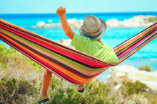 Happy Child By The Sea On Hammock In Greece Background
